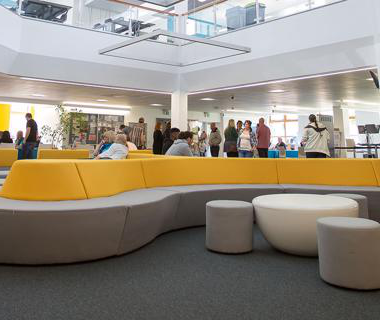 Groups of students walking around and sitting on modern yellow 和 grey sofas in a large, open study space.