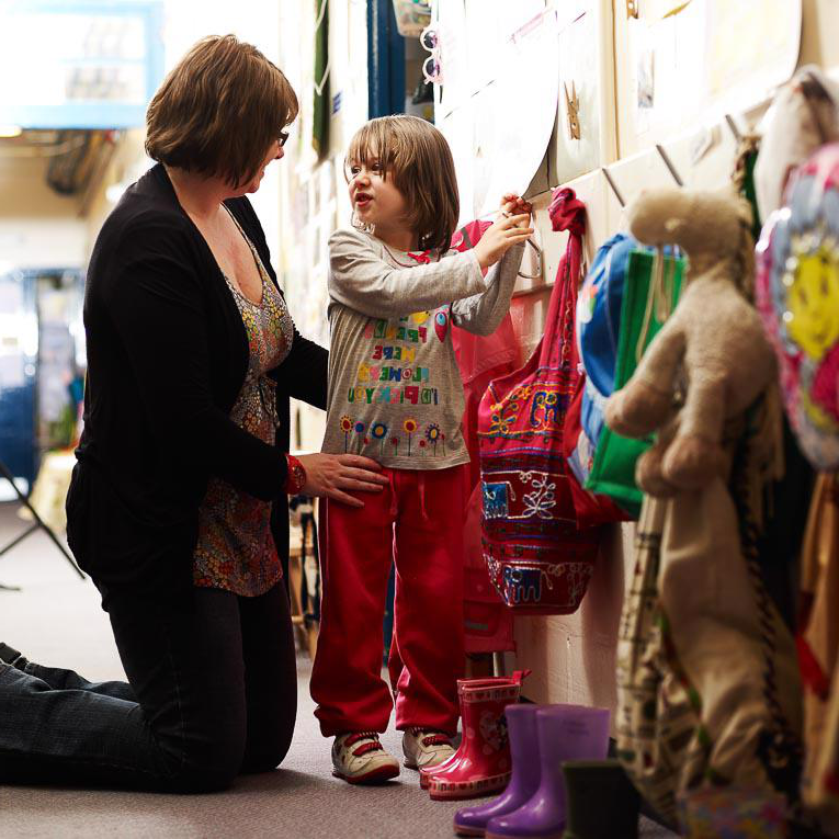 Mother helping child hang coat up at nursery