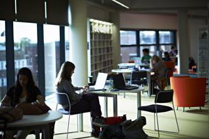 darkened picture of STudents at desks inside the hive library