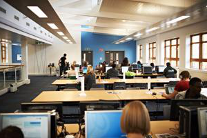view from the back of a room with rows of desks at which STudents are working
