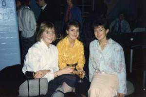 Three women sitting in a nightclub in 1980s clothing