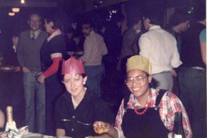 Two women in 1980s clothing 和 paper party hats sit in front of party food