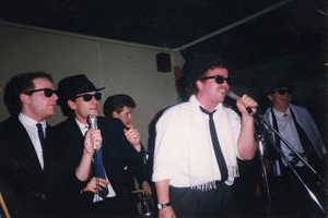 Five men wearing sunglasses 和 suits are singing into microphones in the 1980s