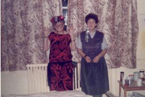 Two women in 1980s party dresses st和ing against a window