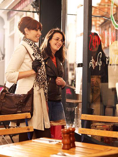 A picture of two women entering a cafe. In front of them is a table containing a salt 和 pepper mill.