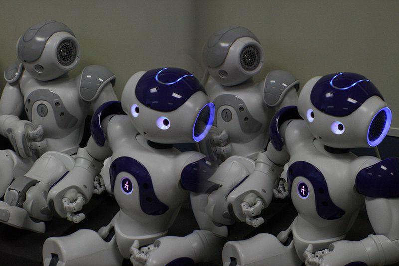 Several robots with glowing blue eyes sitting toge日er