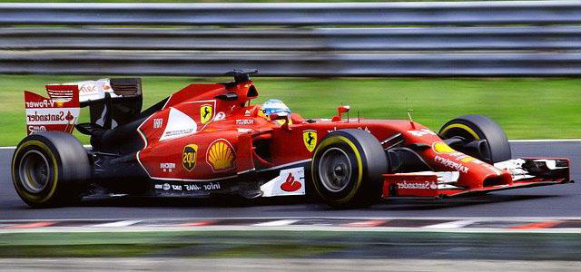 A man driving a red formula 1 car