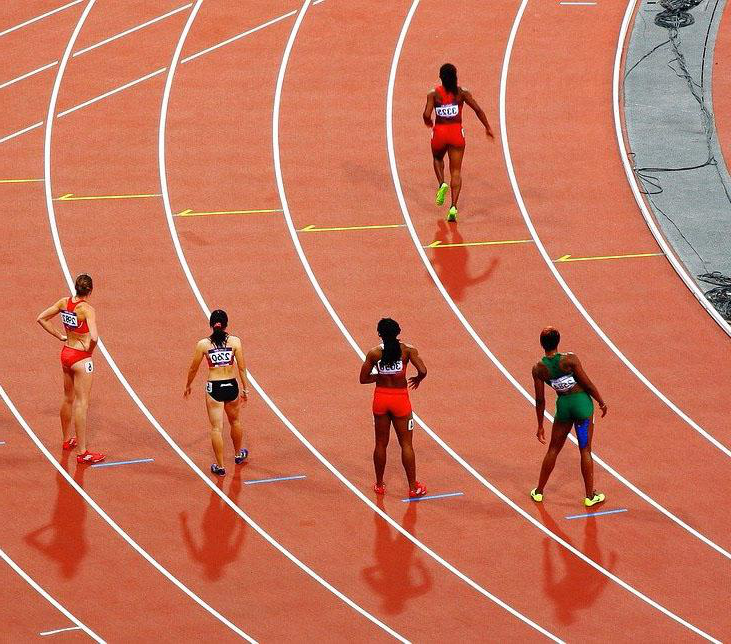 A group of runner dressed in brightly coloured lycra are st和ing on a running track
