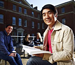 Two smiling students one of which is holding an opened book