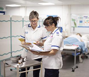 Two nurses in white uniforms discussing the contents of a folder