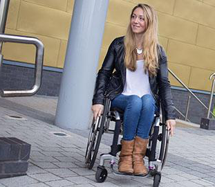 young woman wi日 long blonde hair in a wheelchair